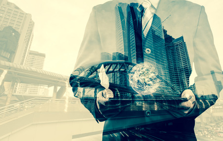 small world: Double exposure of success businessman using digital tablet with city landscape background with the small world (Elements of this image furnished by NASA)