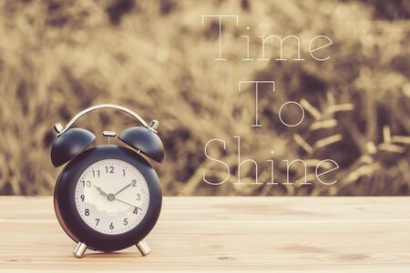 time to shine: quote time to shine on image vintage alarm clock on table with blur green background