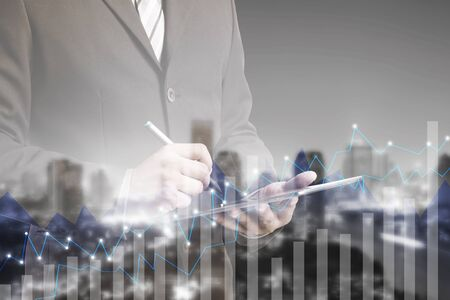 concept and ideas: Double exposure of success businessman using digital tablet with city landscape blurred background.Forex graph on the business city centre. A metaphor of international financial consulting.investment concept