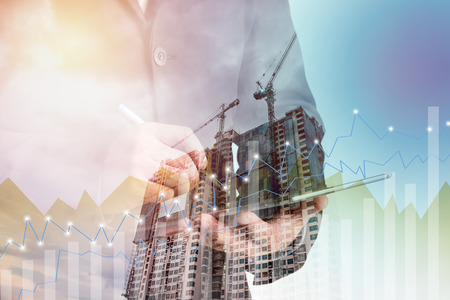 company innovation: Double exposure of success businessman using digital tablet with Construction site with crane and building,business background