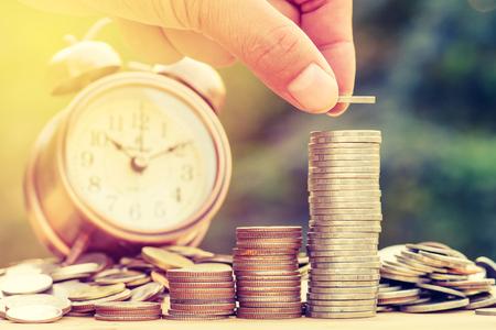 fondos negocios: Cerca de la mano masculina apilar monedas de oro con el fondo verde bokeh, Finanzas y del concepto del dinero, ahorrar dinero para preparar en el futuro.
