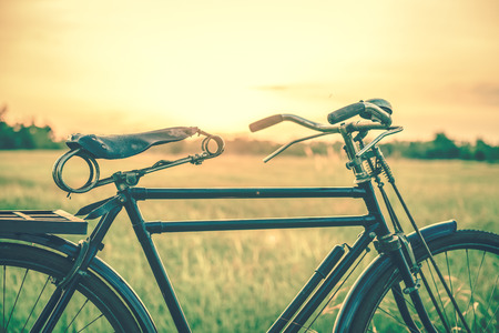 beautiful landscape image with Bicycle at sunset in vintage tone style.classic bicycle,old bicycle style for greeting Cards ,post card