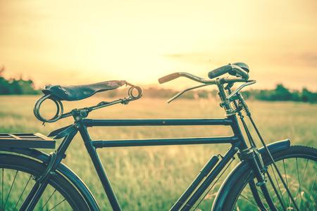 Belle image de paysage avec le vélo au coucher du soleil dans le style de ton vintage. Vélo classique, ancien style de vélo pour cartes de voeux, carte postale