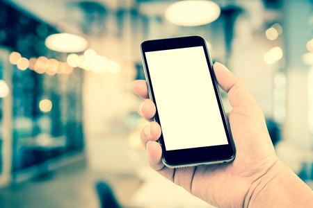 Hand hält die Telefontablette auf verschwommen im Geschäft oder Restaurant Hintergrund; Transaktionen von Smartphone-Konzept