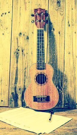 ukelele: Ukulele and musical  paper notes ; vintage filtered style Stock Photo