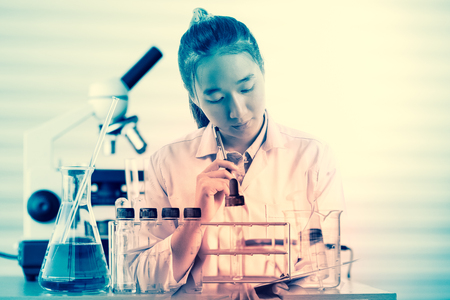 female medical or scientific researcher or woman doctor thinking for write report in a laboratory with her microscope beside her Stock Photo