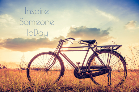 Vintage Bicycle with Summer grassfield ; life quote. Inspirational quote. Motivational background Stock Photo