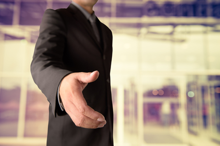 Businessman offering for handshake on office buildings blur background Stock Photo