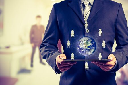 small world: Business man holding tablet pc with business people icons around the small world
