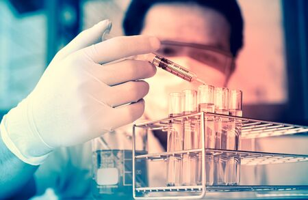 protective goggles: scientist with equipment and science experiments. Investigator checking test tubes. Man wears protective goggles Stock Photo