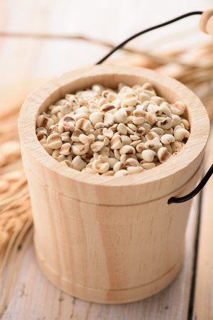 organic millet seeds in a wooden bucket closeup Stock Photo