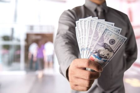 profitable: Businessman with money in hand, US dollar (USD) bills - investment, success and profitable business concepts
