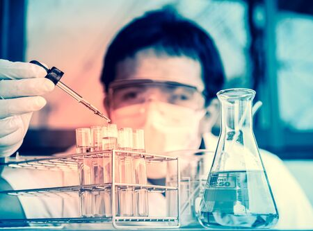 protective goggles: Investigator checking test tubes. Man wears protective goggles Stock Photo