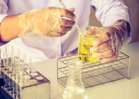 experimenting: scientist are experimenting with yellow chemicals