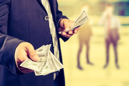 Money in Businessman hand , US dollar,investment, success and profitable business concepts,vintage process style