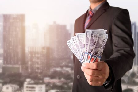 Double exposure of Businessman with money in hand with cityscape blurred building background, US dollar (USD) bills - investment, success and profitable business concepts