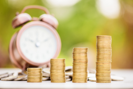 finance concept: Finance and Money concept, Money Gold coin stack growing graph with alarm clock,investment concept