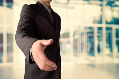 bridging: Businessman offering for handshake on office buildings blur background Stock Photo