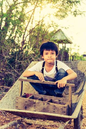 kiddy: Cute Asian boy sit on a cart