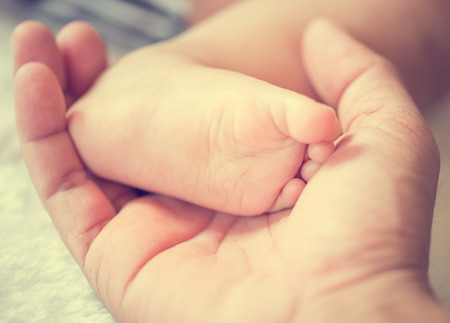 newborn baby feet on male hand,vintage process style Stock Photo