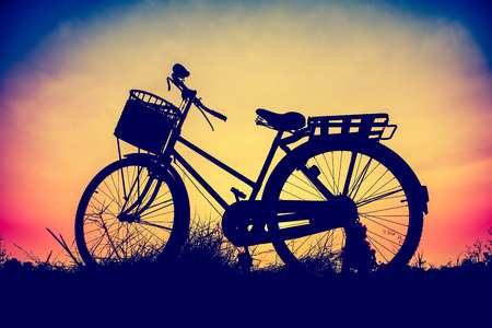 beautiful landscape image with Bicycle at sunset in vintage tone style