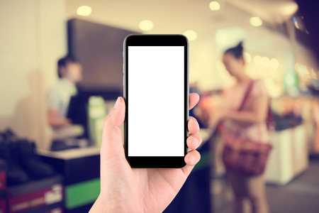 counter service: hand holding the phone tablet on blurred in shop counter service background;Transactions by smartphone concept Stock Photo
