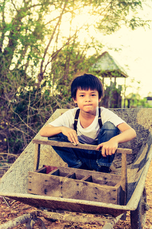 aspirational: Cute Asian boy sit on a cart