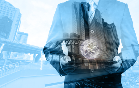 small world: Double exposure of success businessman using digital tablet with city landscape background with the small world