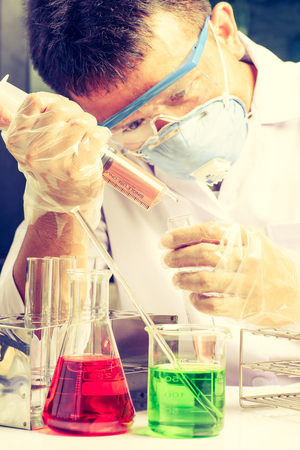 Hands of scientist holding tools during scientific experiment in laboratory Stock Photo