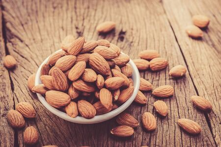 grained: almonds in a white ceramic bowl on grained wood background Stock Photo