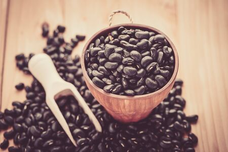 black beans: Vigna mungo or black beans in wooden cup with wooden scoop