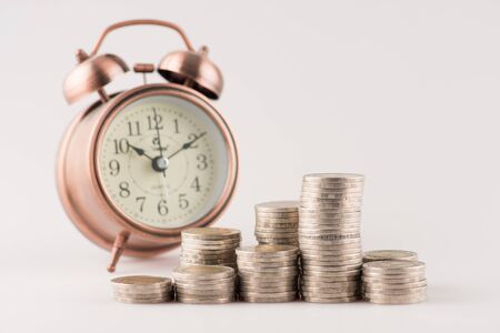 Close up of stacking gold coins with alarm clock ,Business Finance and Money concept,Save money for prepare in the future. Stock Photo