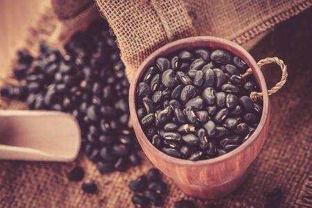 vigna: Vigna mungo or black beans in wooden cup with wooden scoop on sack background Stock Photo
