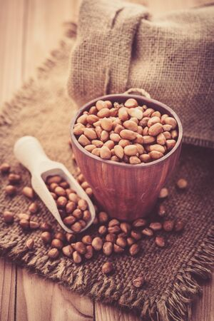 earthnuts: close up of raw peanuts or arachis in wood cup on sack background