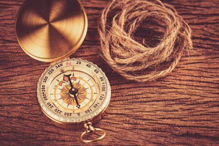 Gold Compass with rope on the old wood