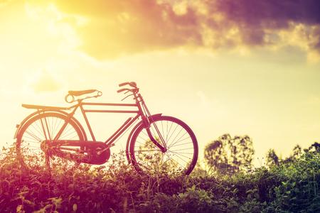 Mooi landschap afbeelding met klassieke fiets bij zonsondergang