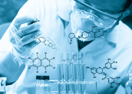 scientist  dropping chemical liquid to flask with lab glassware background, Laboratory research concept,Researcher is dropping the reagent into test tube, with chemical equations background, in laboratory