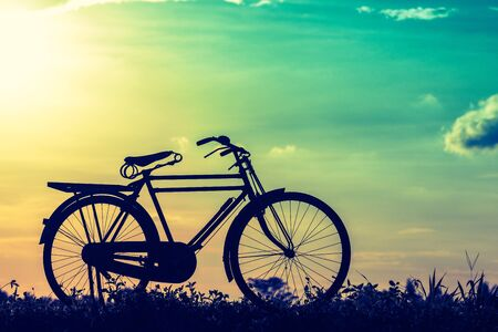 beautiful landscape image with Silhouette Bicycle at sunset vintage tone style