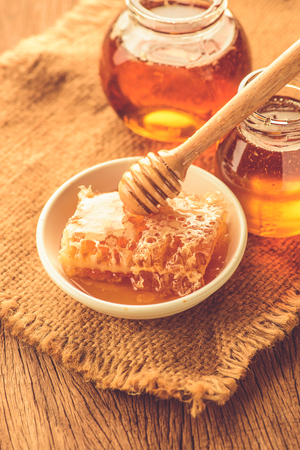 drizzler: Honey  with honeycomb in white ceramic bowl and wooden drizzler