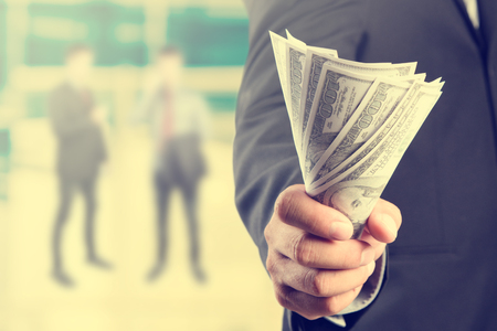 Geld in de hand van de zakenman, de Amerikaanse dollar, de investeringen, succes en winstgevende business concepten, uitstekende proces stijl