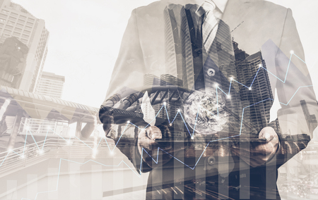 small world: Double exposure of success businessman using digital tablet with city landscape background.Forex graph oon the business city centre. A metaphor of international financial consulting.investment concept with the small world (Elements of this image furnished