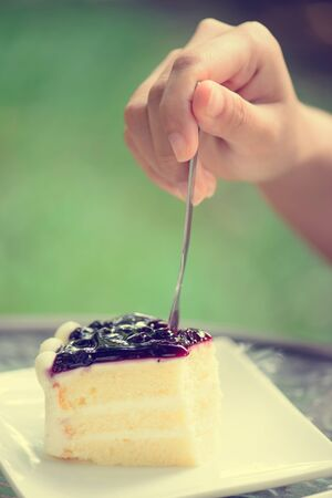 confiserie: Blueberry cake with woman hand and fork Stock Photo
