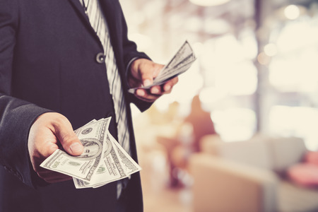 Businessman with money in hand, US dollar (USD) bills - investment, success and profitable business concepts,vintage process style