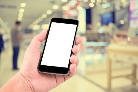 hands  hour: Smart phone with white screen in hand on blurred in shopping mall background