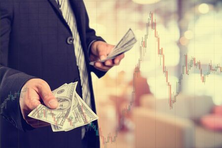 Businessman with money in hand, US dollar (USD) bills - investment, success and profitable business concepts.with stock chart, investment concept. Stock Photo