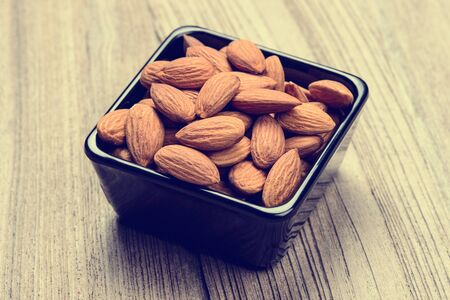 almonds in a ceramic bowl on grained wood background.Almonds for background. Stock Photo