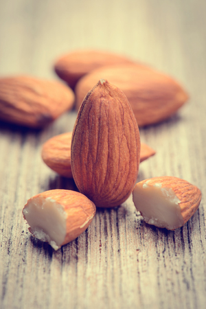 Close up of a pile of almonds.almonds for background.almonds on wood table.