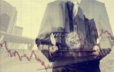 small world: Double exposure of success businessman using digital tablet with city landscape background.with stock chart, investment concept. with the small world (Elements of this image furnished by NASA)