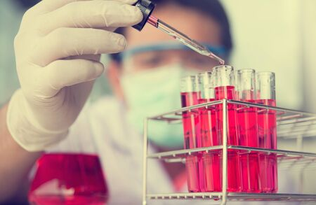 wears: Glass laboratory chemical test tubes with red liquid.Man wears protective goggles Stock Photo