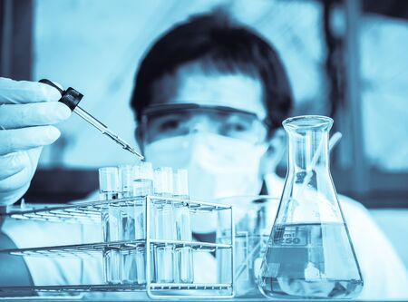 wears: Investigator checking test tubes. Man wears protective goggles Stock Photo